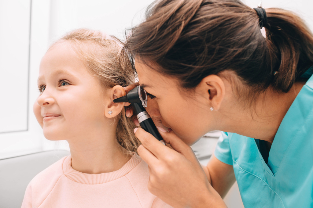 Smiling little girl having ear exam with otoscope